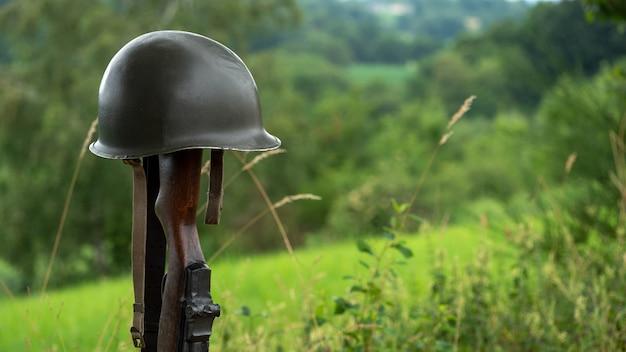 Cruz conmemorativa del campo de batalla con el símbolo de un soldado estadounidense caído rifle m1 con casco