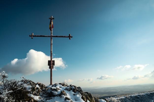 Cruz cristiana de metal de pie sobre la roca con una bandera