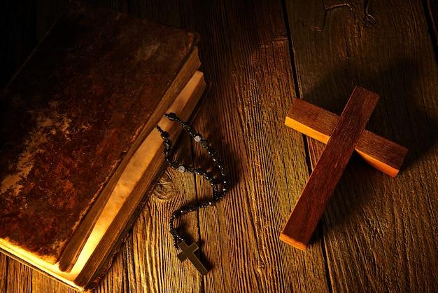 Cruz cristiana sobre biblia de madera y rosario.