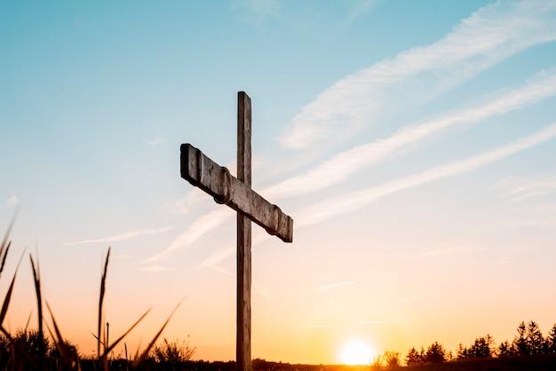 Una cruz de madera artesanal sobre el cielo.