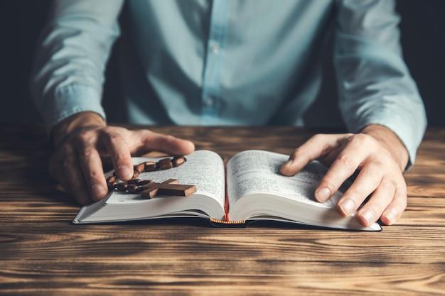Cruz de la mano del hombre de oración en la santa biblia en la mesa de madera