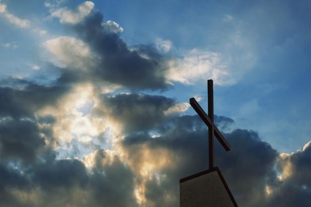 Cruz silueta con la puesta de sol como fondo