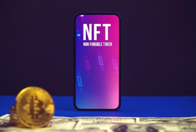 Cryptoart y criptográfico, logotipo de token nft en la pantalla del teléfono móvil moderno, mesa de oficina con bitcoins de dólar y cripto
