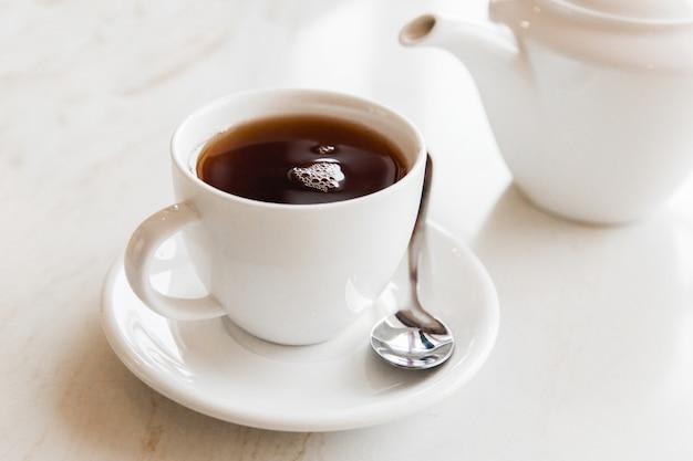 Cu blanco del té negro en la tabla blanca en el café. desayuno con taza de té.