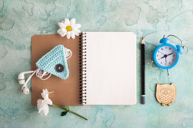 Cuaderno abierto, auriculares, despertador