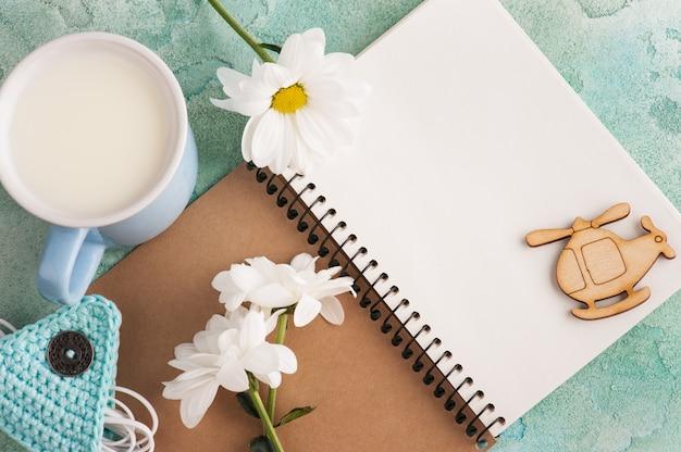 Cuaderno abierto, auriculares, taza de leche.