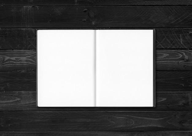 Cuaderno abierto en blanco aislado sobre fondo de madera negra