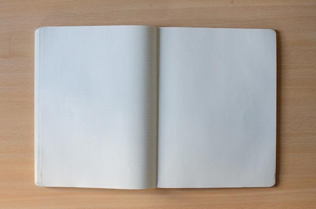 Cuaderno abierto en blanco blanco con mucho espacio de texto sobre un fondo de madera