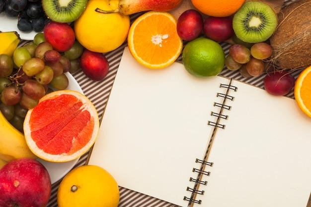 Un cuaderno abierto en blanco con muchas frutas frescas.