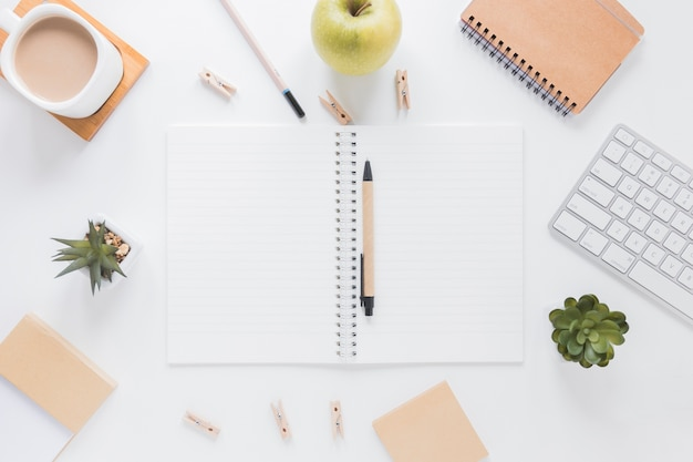 Cuaderno abierto con bolígrafo cerca de papelería y manzana en mesa blanca