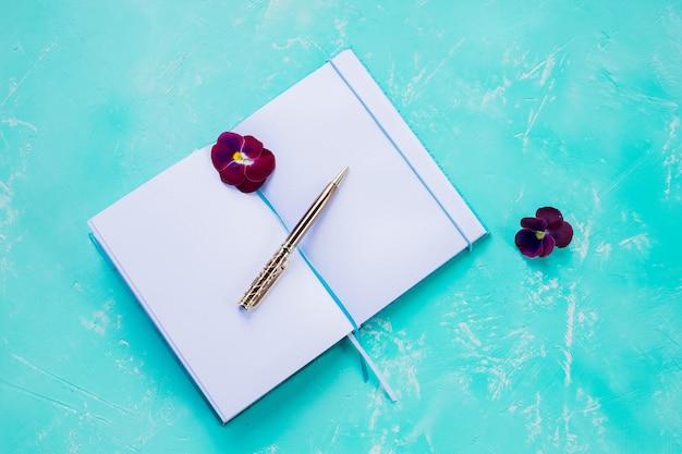Cuaderno abierto con bolígrafo.
