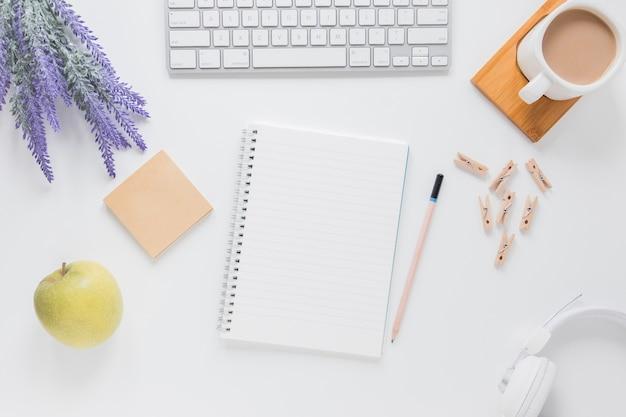 Cuaderno abierto cerca de papelería en mesa blanca con gadgets y taza de café