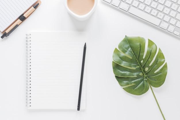 Cuaderno abierto cerca de la taza de café y el teclado en la mesa con hoja verde