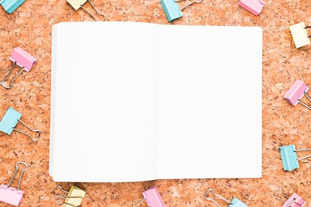 Cuaderno abierto y clips de carpeta multicolores.