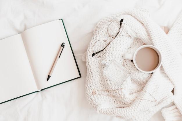 Cuaderno abierto con pluma cerca de suéter con cosas en sábana