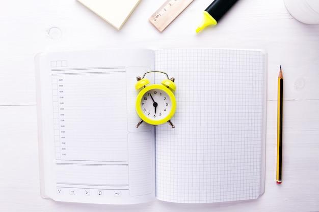 Un cuaderno abierto con despertador y material de oficina.