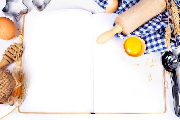Cuaderno abierto e ingredientes básicos para hornear