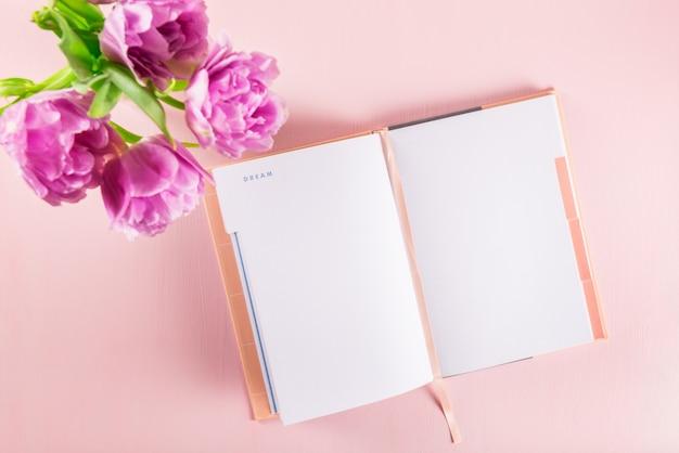Cuaderno abierto para escribir sueños e ideas con flores cerca