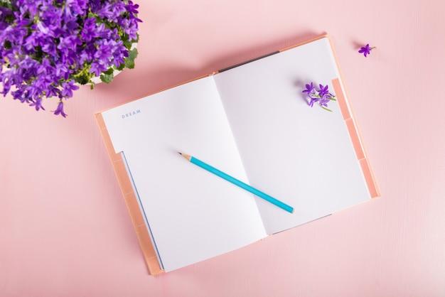 Cuaderno abierto para escribir sueños e ideas con flores cerca.