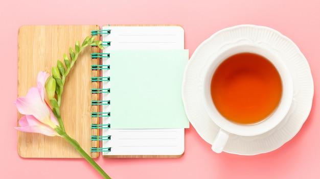 Cuaderno abierto con espacio de copia taza de té y flor de fresia rosa