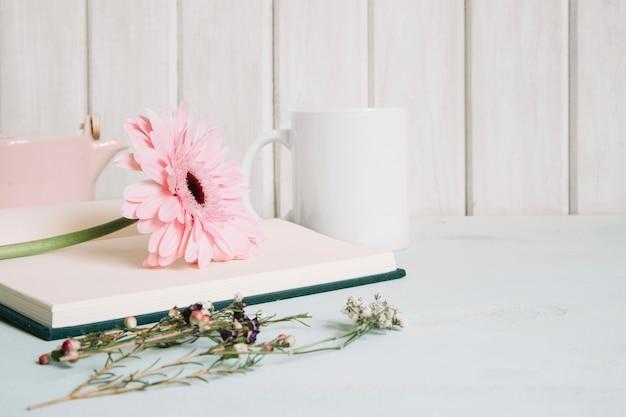Cuaderno abierto con flor junto a la taza