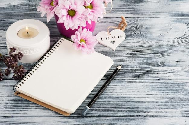 Cuaderno abierto con flores de margarita rosa