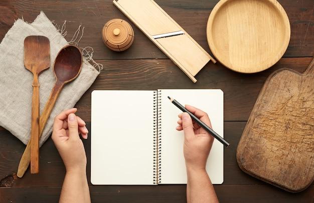 Cuaderno abierto con hojas blancas en blanco y utensilios de cocina en una mesa de madera marrón, manos femeninas sostienen un lápiz negro, vista superior
