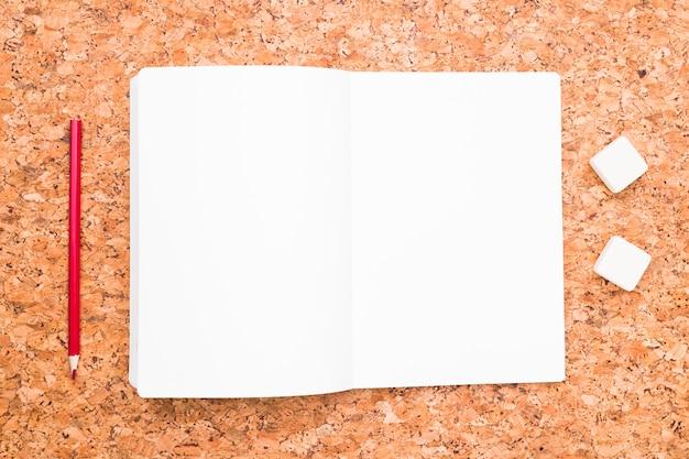 Cuaderno abierto junto a lapiz y gomas de borrar.