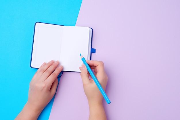 Cuaderno abierto y lápiz azul de madera en una mano derecha femenina
