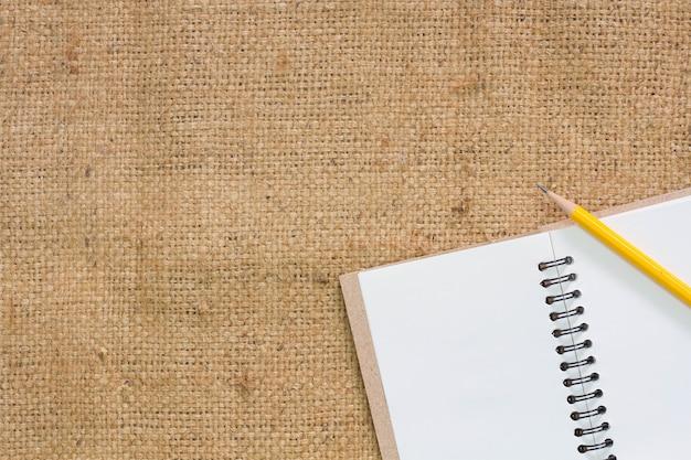 Cuaderno abierto y lápiz en la mesa de tela de saco.