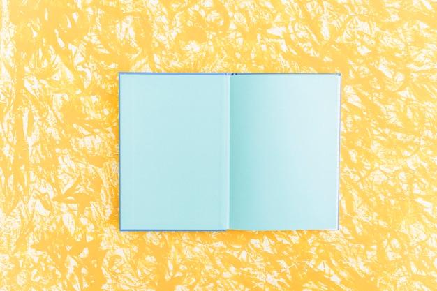 Un cuaderno abierto de páginas azules sobre fondo amarillo con textura