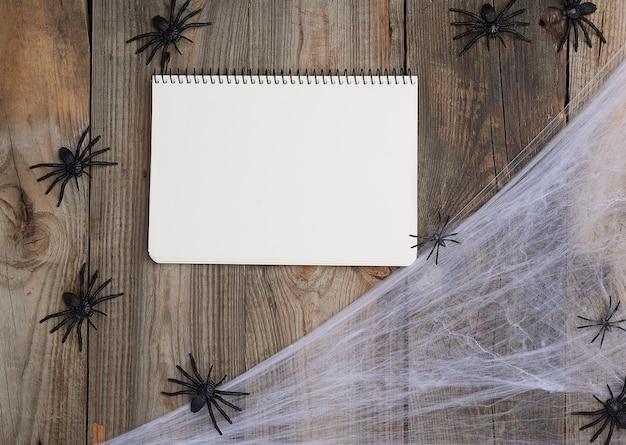 Cuaderno abierto con páginas en blanco en blanco, telaraña y arañas negras