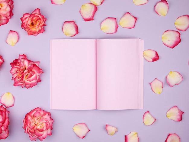 Cuaderno abierto con páginas en blanco rosa