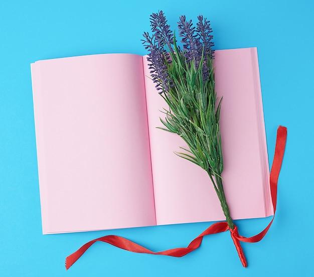 Cuaderno abierto con páginas rosas en blanco, ramo de lavandas sobre una superficie azul