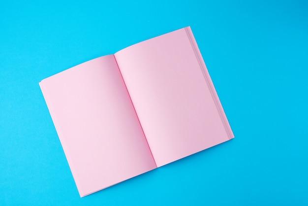Cuaderno abierto con páginas rosas en blanco sobre un espacio azul, vista superior