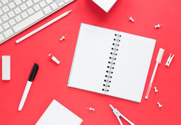 Cuaderno abierto y papelería en superficie roja