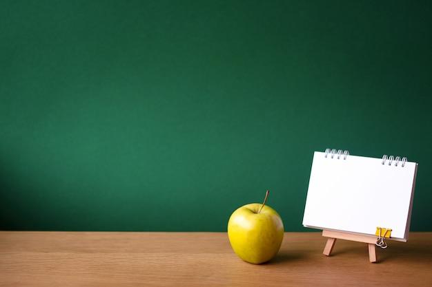 Cuaderno abierto sobre caballete en miniatura y manzana verde