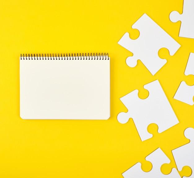 Cuaderno abierto sobre un fondo amarillo, junto a grandes rompecabezas en blanco