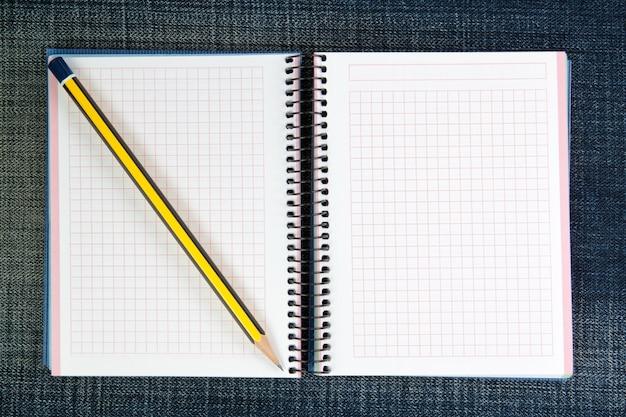 Un cuaderno abierto sobre jeans y un lápiz.