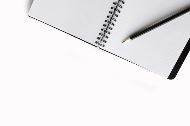 Cuaderno abierto sobre mesa blanca con lapiz