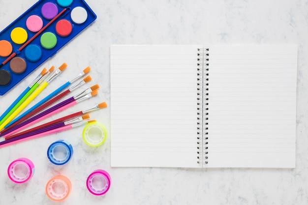Cuaderno abierto con suministros de pintura.