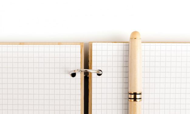 Cuaderno abierto con tapa de madera y páginas a cuadros.