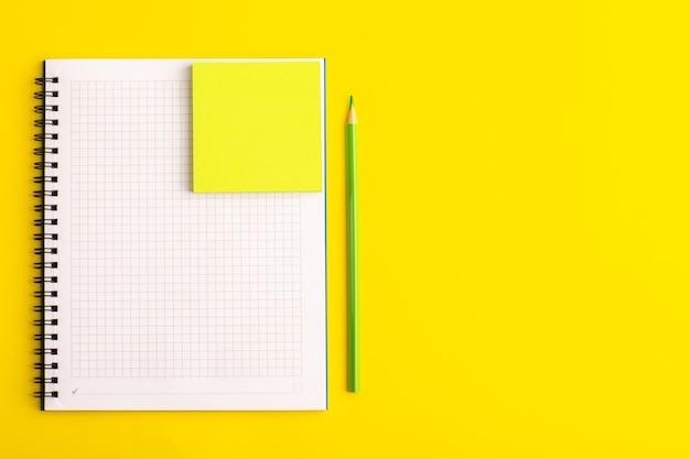 Cuaderno abierto de vista frontal con adhesivo amarillo sobre escritorio amarillo