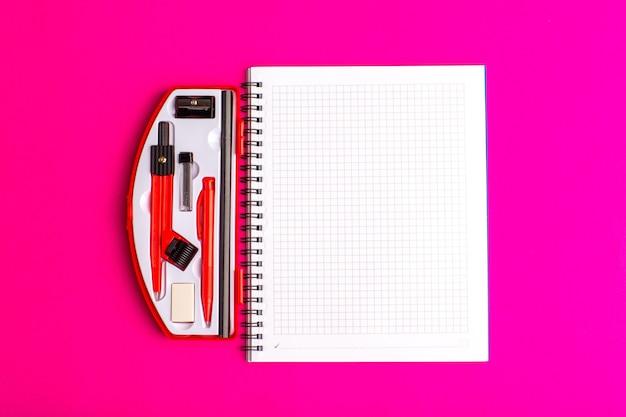 Cuaderno abierto de vista frontal con figuras geométricas en superficie púrpura