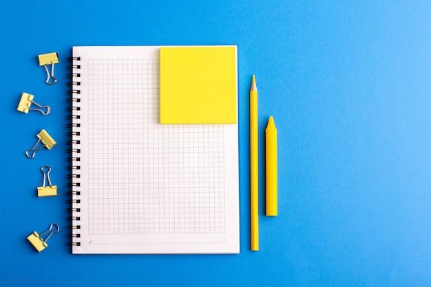 Cuaderno abierto de vista frontal con pegatinas y lápiz sobre la superficie azul