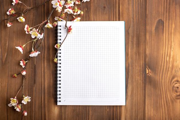 Cuaderno abierto de vista superior con flores en el escritorio marrón