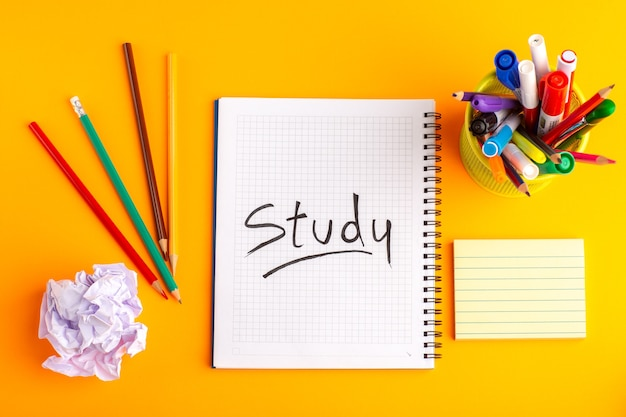 Cuaderno abierto de vista superior con lápices de colores sobre la superficie naranja