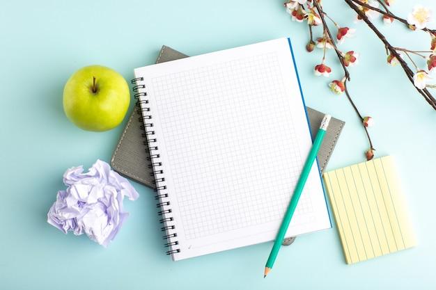 Cuaderno abierto de vista superior con manzana verde y lápiz sobre superficie azul claro