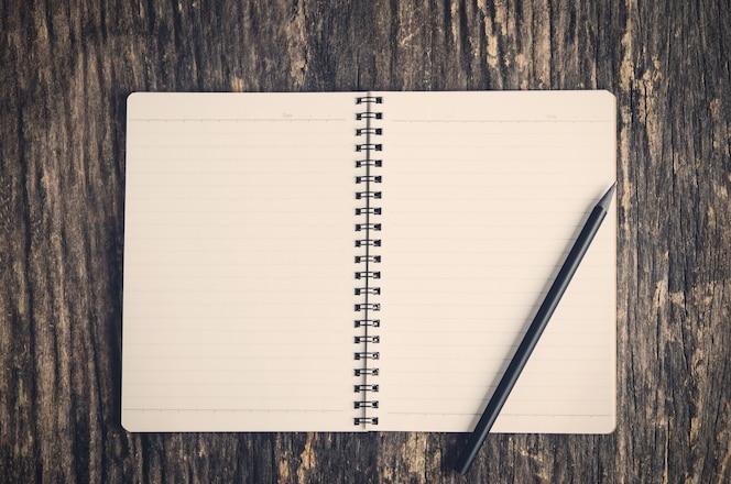 Cuaderno abierto y lápiz negro