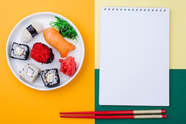 Cuaderno al lado del plato con sushi